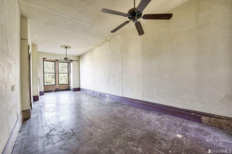 A large empty room with ceiling fan