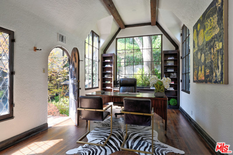 home office with vaulted and beamed ceilings and zebra-skin rug on floor