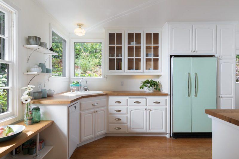 A white kitchen with a sink, aqua fridge and corner window