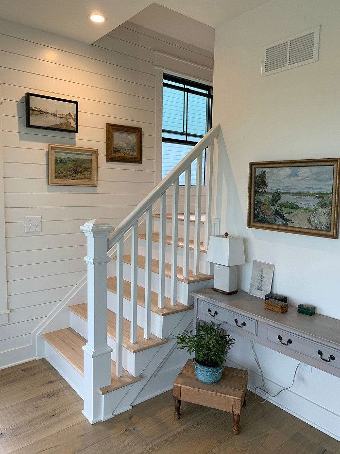 staircase with shiplap wall and window