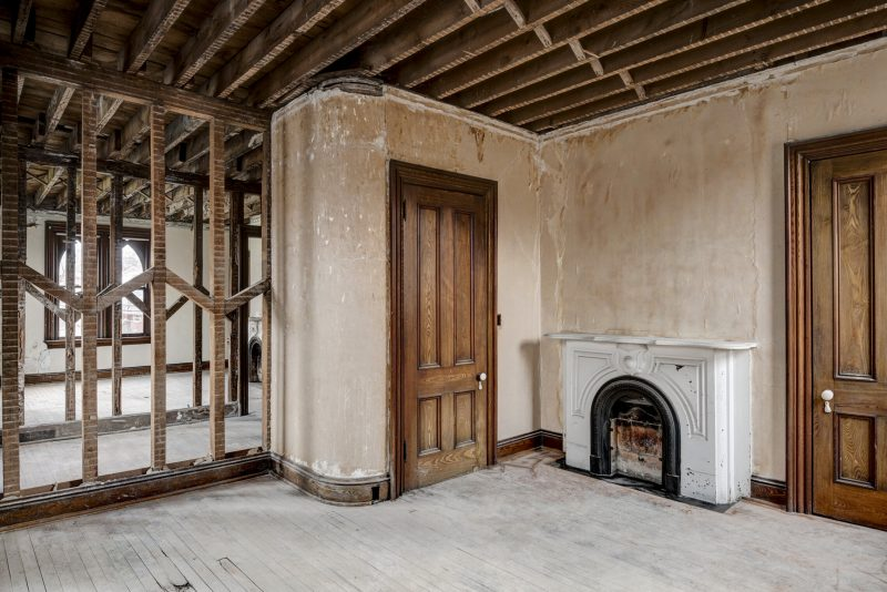 Unfinished room with a wooden closet door and vintage fireplace