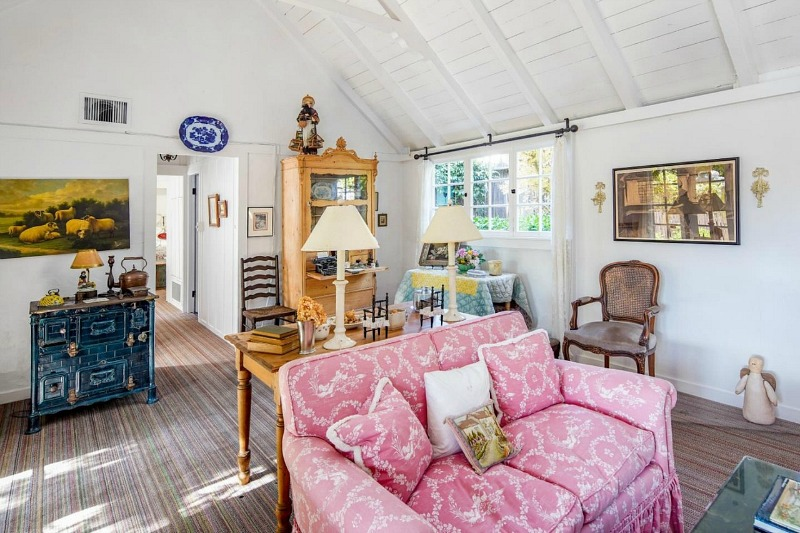cottage living room with pink sofa and vaulted ceilings