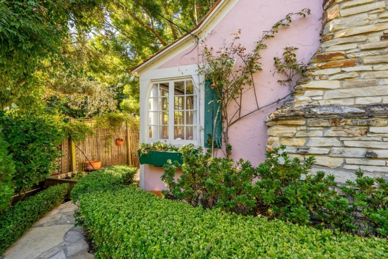 exterior corner of pink cottage with shutters