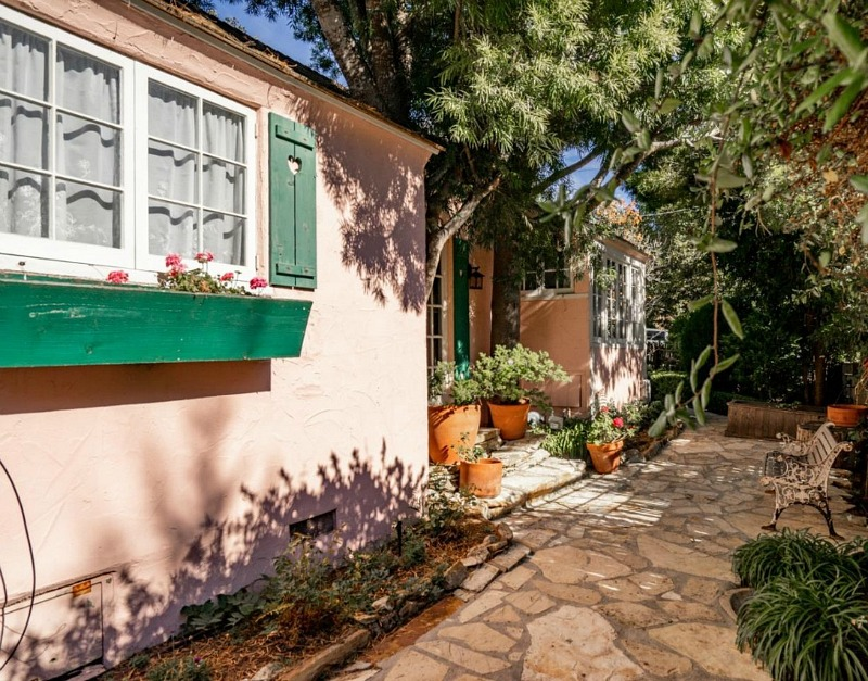 front of pink cottage with window boxes and shutters