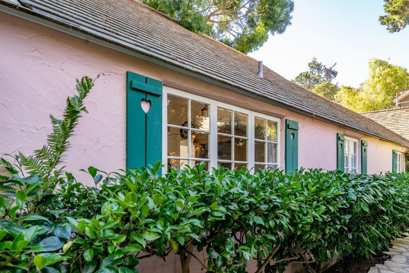 front of pink cottage in Carmel with shutters