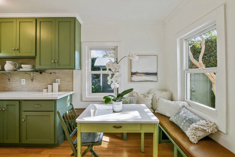 green kitchen cabinets and banquette in farmhouse kitchen