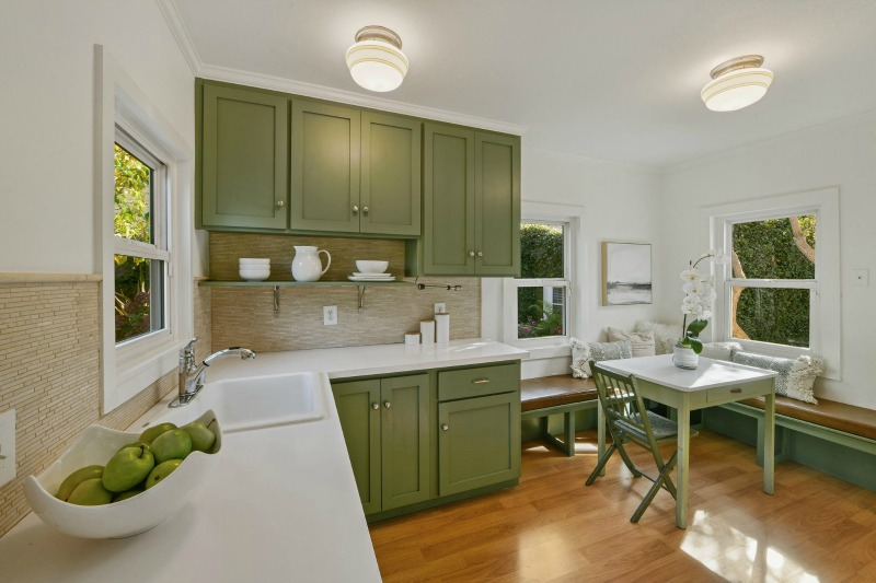 green kitchen cabinets and banquette in small farmhouse kitchen