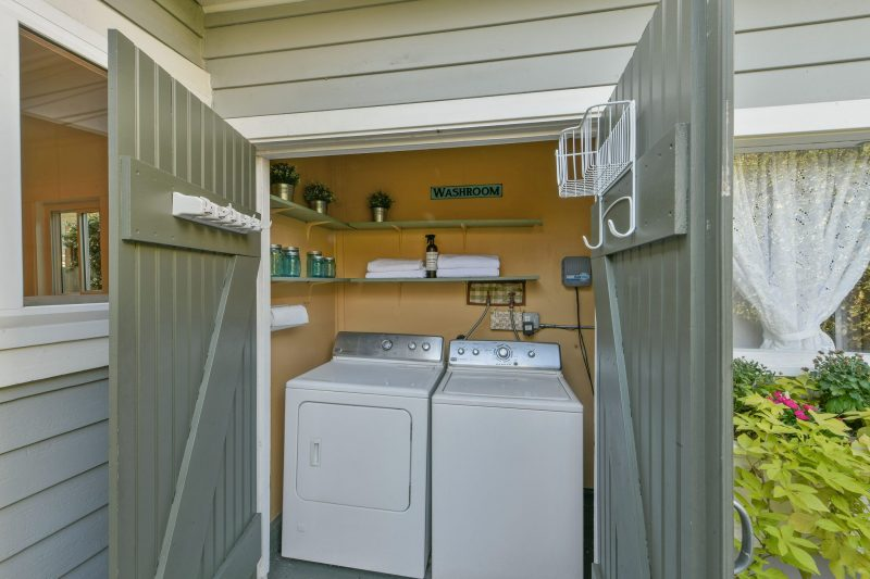 laundry shed behind house with washer and dryer