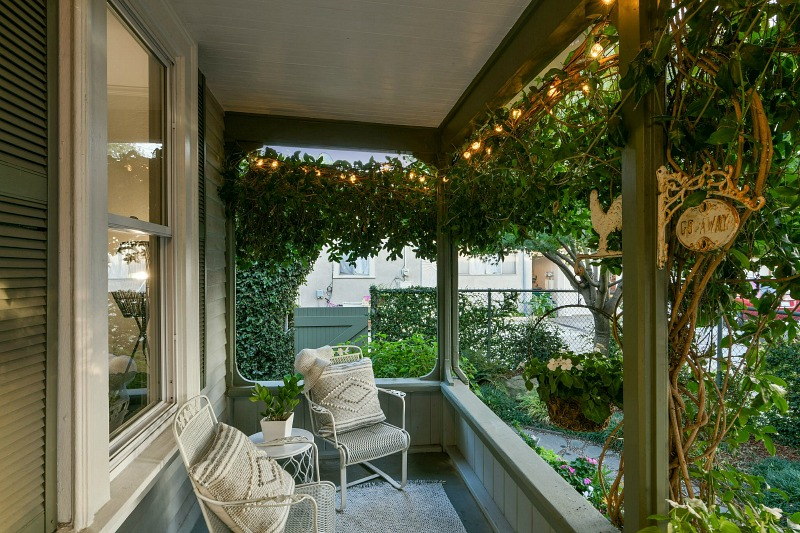 small farmhouse ivy-covered front porch with twinkle lights